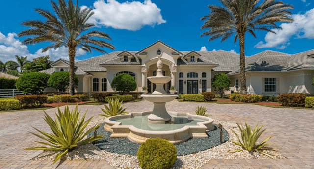 photograph of large home with fountain in the middle